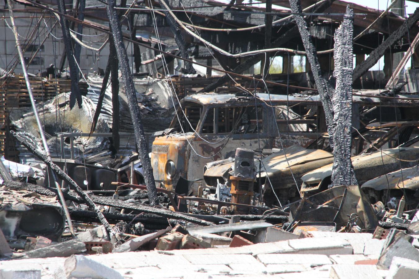 Tussen de uitgebrande auto's valt het silhouet van een Volkswagenbusje op.