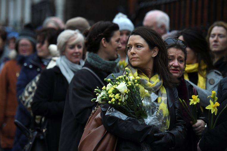 Oud-klasgenotes van O'Riordan hebben bloemen bij.