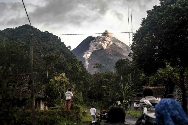 Inwoners van Java stoppen op de weg om te kijken naar de vulkaan Merapi die as en stenen spuwt. De Merapi is de meest actieve vulkaan van Indonesië.  Beeld AFP