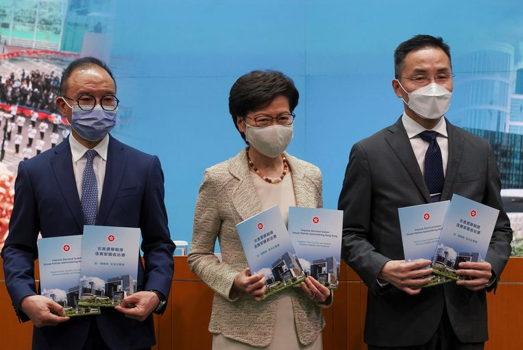 De Hongkongse bestuurder Carrie Lam (midden) met twee collega's tijdens een persconferentie over de veranderingen in de kieswet.  Beeld REUTERS