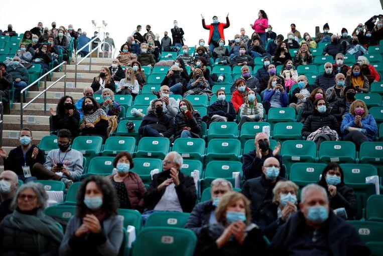Leden van het publiek dragen maskers en luisteren naar muziek na het tonen van hun
