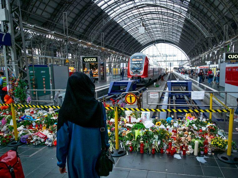 Bloemen en kaarsen herinneren aan de afschuwelijke moord in het station van Frankfurt. Beeld AP