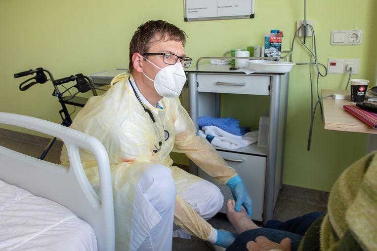Selmer Lauwers controleert een patiënt op de covid-afdeling.  Beeld ETZ / Maria van der Heyden