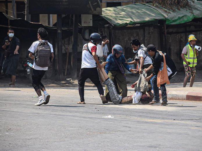 Een beschoten demonstrant wordt weggedragen in de stad Myingyan.
