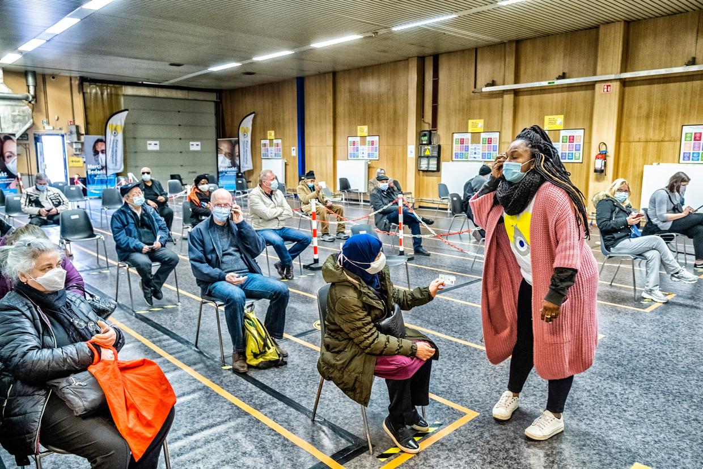Mensen wachten op hun beurt om geprikt te worden in een vaccinatiecentrum in Molenbeek. Beeld Tim Dirven