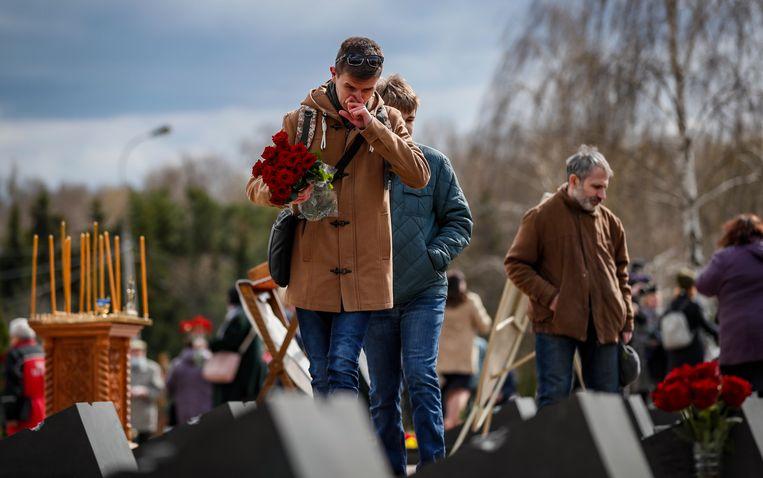 Een man rouwt bij het graf van een slachtoffer van de kernramp. Beeld EPA