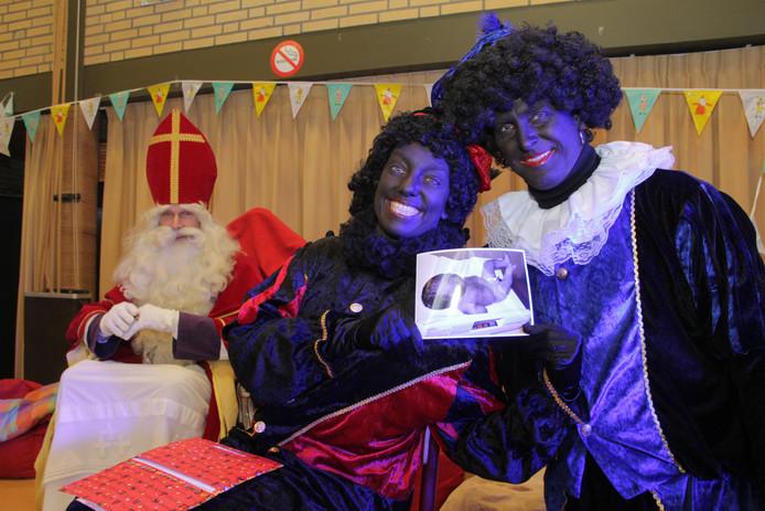 Amora en Pedro laten trots de foto van de pasgeboren Finn zien. Sinterklaas kijkt instemmend toe.