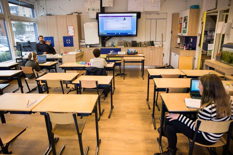 Meester Steven geeft online les aan groep 8 vanuit de klas. Drie kinderen zijn wel op school een vanwege slechte wifi en eentje heeft er extra hulp nodig. Beeld Arie Kievit / de Volkskrant