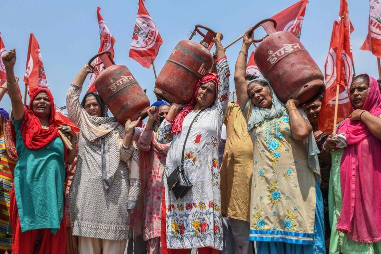 Met gasflessen op hun schouders protesteren vrouwen in de Indiase stad Amritsar tegen de stijgende gas- en benzineprijzen in het land. Beeld AFP