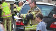 Jongen vraagt handtekeningen van brandweerlui na brand in de straat