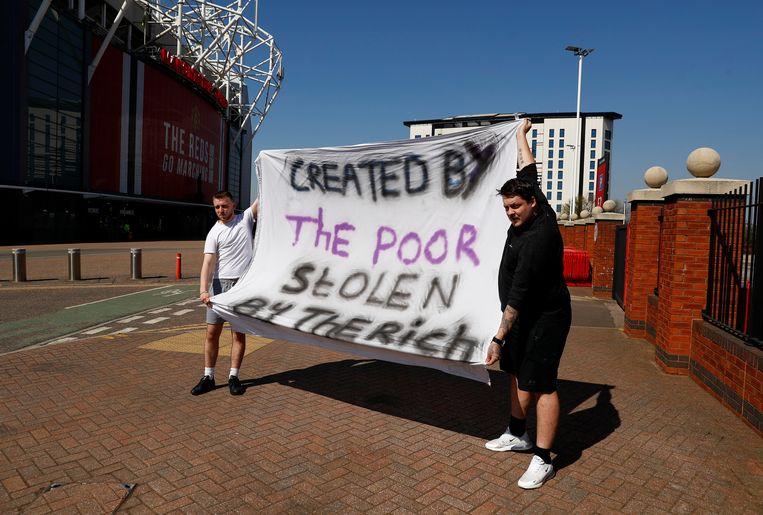 Manchester United fans houden een anti Super League spandoek op voor het Old Trafford stadion in Manchester. Beeld Reuters