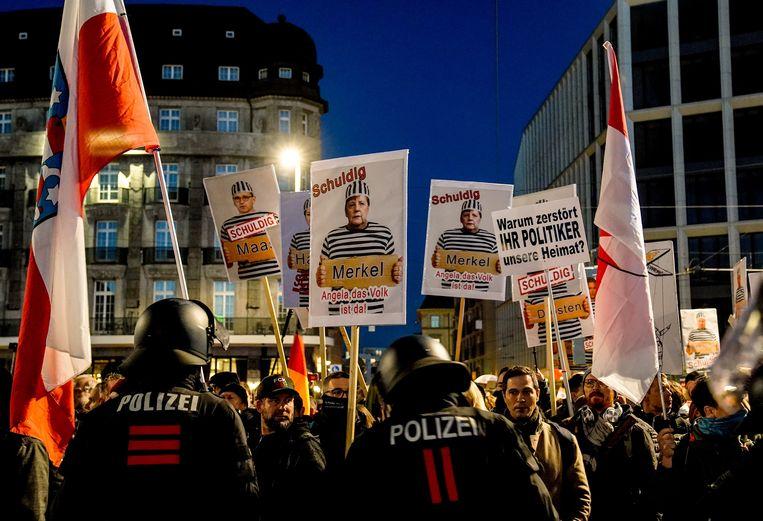 Een demonstratie van de zogeheten Querdenken-beweging tegen het coronabeleid in Leipzig, 7 november. Hier en daar zwaaien mensen met een klein vlaggetje met de letter Q, het teken van QAnon. Beeld EPA