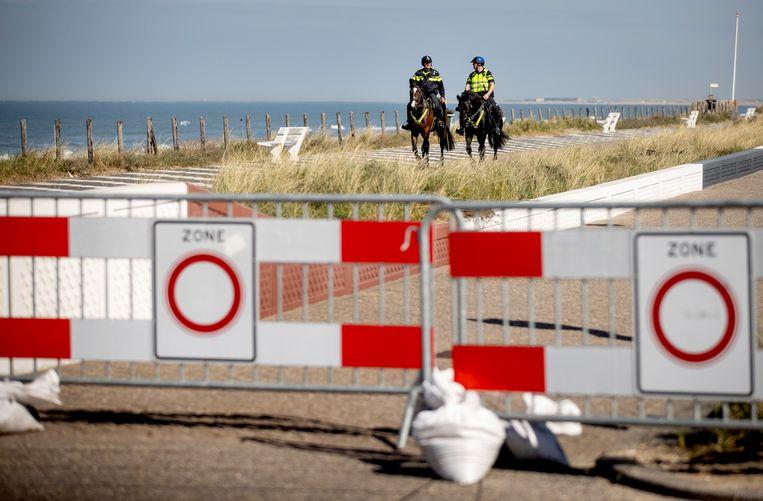 Politie te paard patrouilleert op de boulevard langs het strand. Beeld ANP