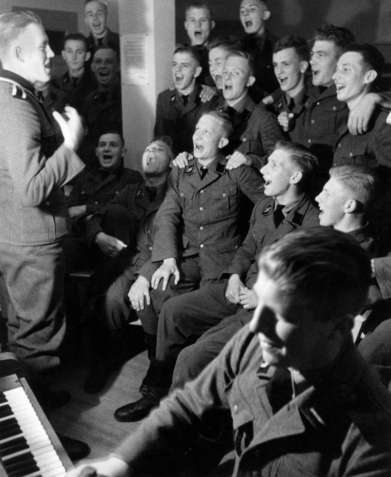 Propagandabeeld van zingende SS-vrijwilligers. Voor veel moderne Duitsers zijn nazi's wezens van een andere planeet. Beeld ullstein bild via Getty Images