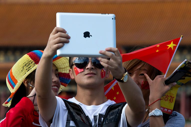 A man holds an iPad as he takes self portraits of him with his friends on Tiananmen Square, on the National Day, the 64th anniversary of the founding of the People's Republic of China, in Beijing, Tuesday, Oct. 1, 2013. Tens of millions of Chinese travel and visit tourist attractions to spend their week-long National Day holidays. (AP Photo/Alexander F. Yuan) Beeld null