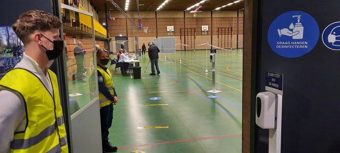 Studenten van het Koning Willem 1 College wijzen stemmers op de hygiënemaatregelen en waar ze kunnen stemmen.