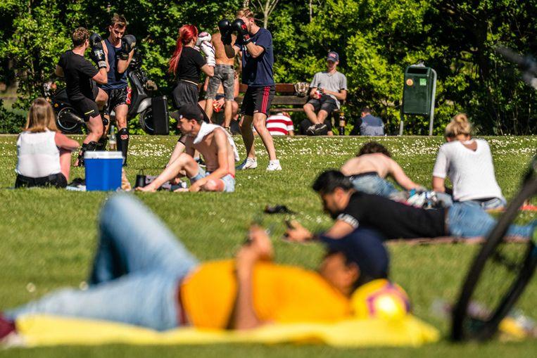 Mensen genieten van de zon bij de Karpendonkse Plas in Eindhoven. Beeld ANP