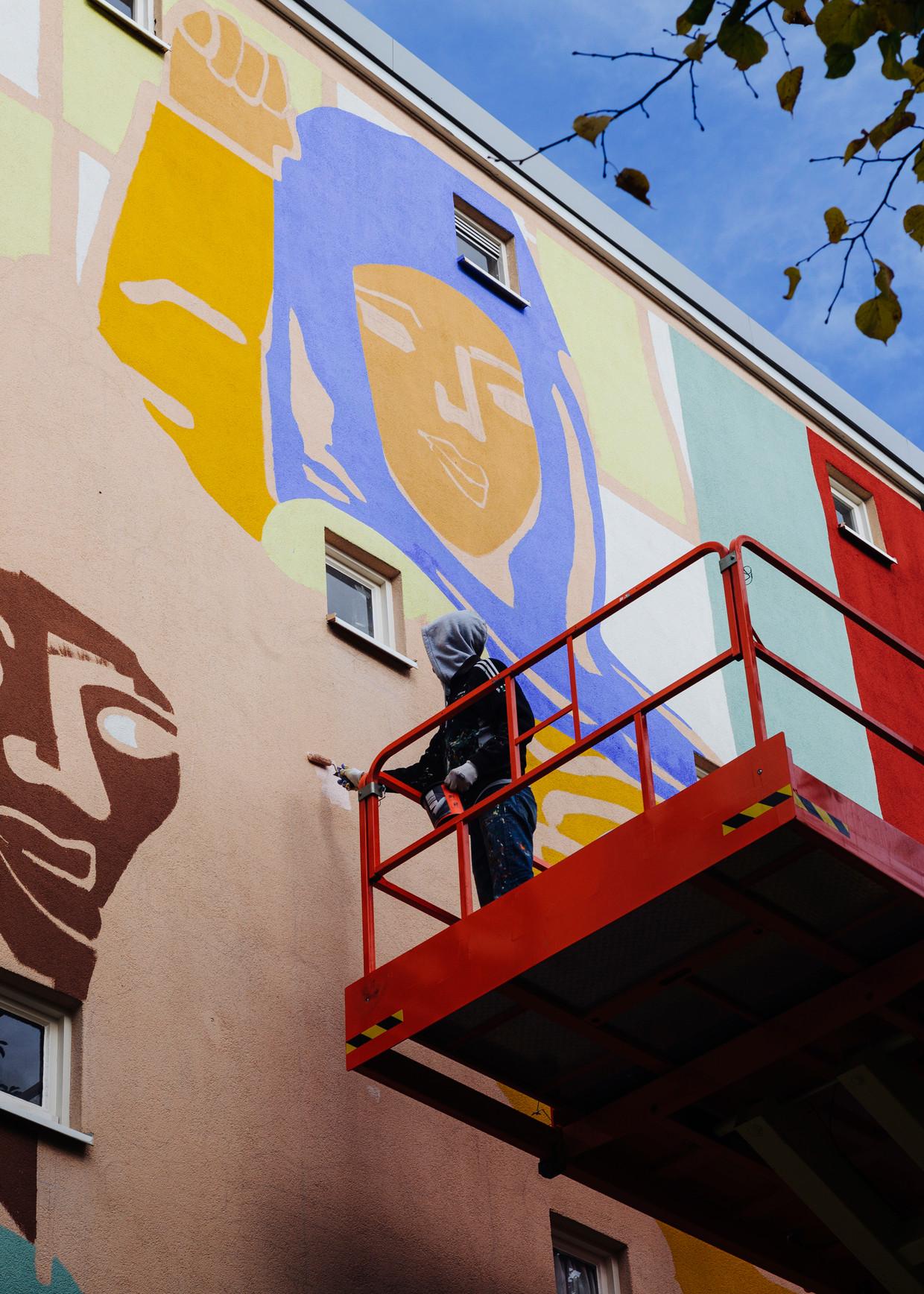 Een schilder aan het werk met de muurschildering van Irée Zamblé. Buurtproject aan de Wiltzanghlaan in Amsterdam West.
