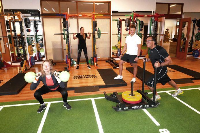 Paola (l.) sport sinds 2 januari mee met haar dochter Izay en haar man Recep Isik. Personal trainer Tony de Zwart van Caesar Fitness + Spa Resort kijkt toe.