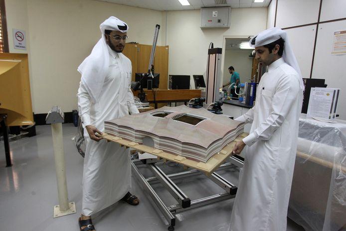 Twee ingenieurs met een 3d-print van het WK-stadion Al Bayt.