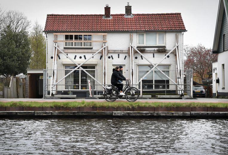 Twee gestutte huizen langs het kanaal Almelo-De Haandrik. Zo'n vierhonderd huizen aan het kanaal hebben schade opgelopen na werkzaamheden. Er komt nu extra geld beschikbaar voor herstel. Beeld Marcel van den Bergh