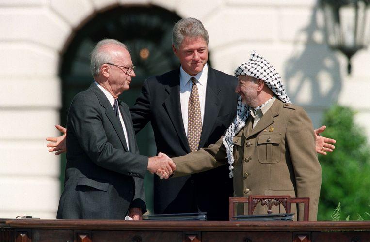 Israëlisch premier Yitzhak Rabin en Palestijns leider Yasser Arafat schudden elkaar de hand in 1993, onder goedkeurend oog van toenmalig Amerikaans president Clinton. Beeld AFP