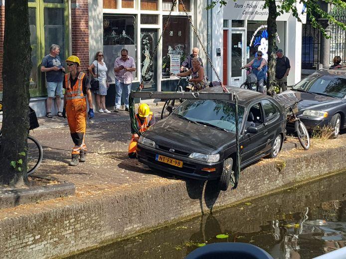 Parkeren gaat mis bij gracht Koornmarkt in Delft.