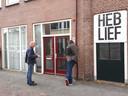 Een ambtenaar van de gemeente Zwolle (l) legt uit aan coffeeshophouder Pascal Leferink (r) waarom het pand gesloten wordt.