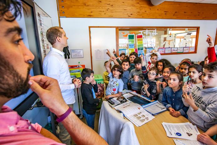 Medewerkers van Sportbedrijf Deventer vertellen aan groep vijf van kindcentrum Rivierenwijk over Happy Life, een speciale server voor het populaire spel Minecraft.