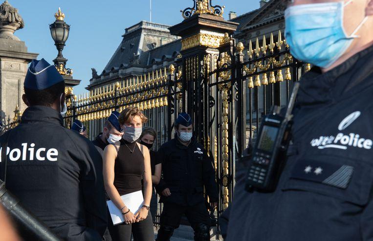 De politie neemt Anuna De Wever mee naar het commissariaat. Samen met twaalf andere activisten krijgt ze een GAS-boete.  Beeld BELGA