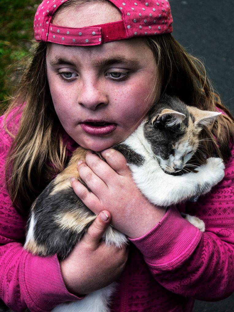 'Ze was gewelddadig, grillig, schreeuwerig. Toen we na het wandelen terugliepen voor de lunch, vond ze deze kat. Ik was bang dat ze hem pijn zou doen, maar plotseling was ze alleen nog maar lief. De kat knuffelde háár.' Beeld Lionel Jusseret