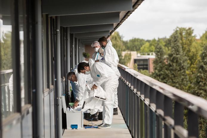 Forensische en technische rechercheurs doen onderzoek op de vierde galerij van de flat aan de Weegbreestraat.