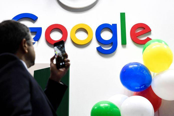 Een man neemt een foto van het Google-logo.