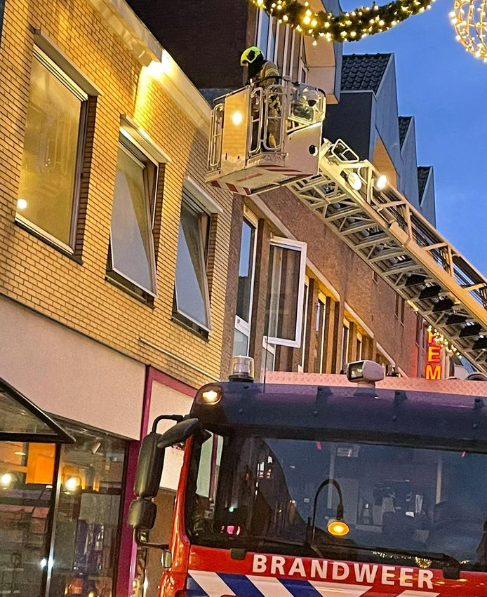 De brandweer controleert vanuit een hoogwerker de eerste etage van het leegstaande winkelpand waarin brand uitbrak.