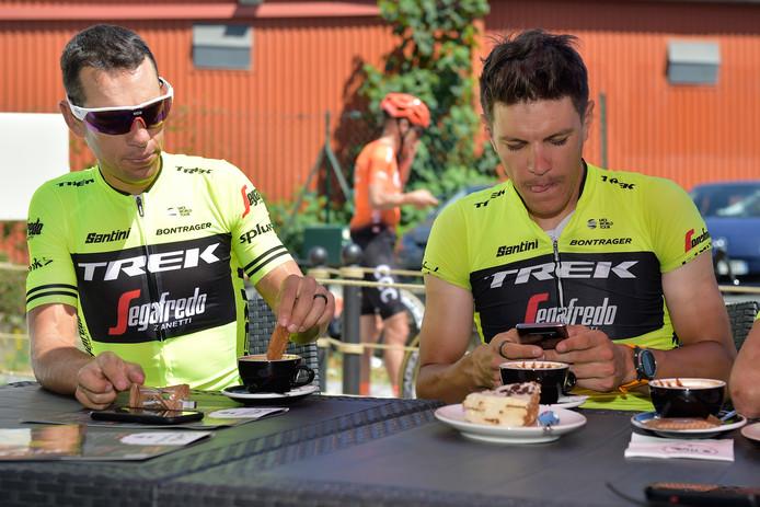 Richie Porte (l) doopt zijn koekje in de koffie. Jasper Stuyven checkt zijn mobieltje voor hij aan zijn stuk taart gaat beginnen.