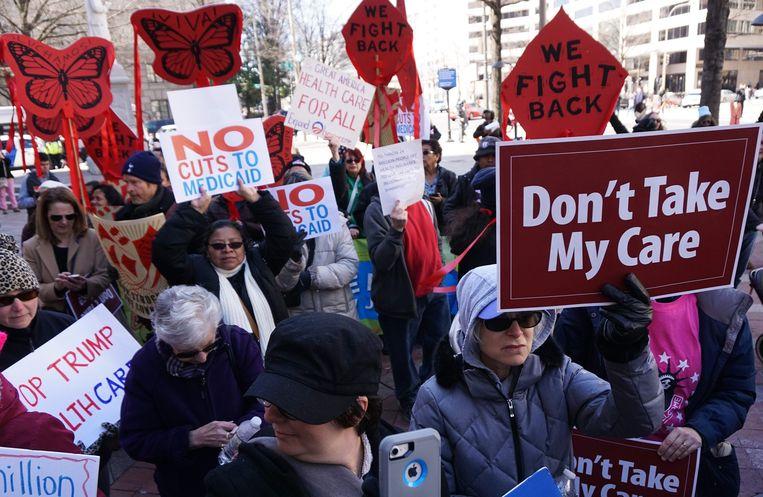 Amerikanen demonstreren voor het behoud van Obamacare voor Trump International Hotel, in Washington DC.  Beeld AFP