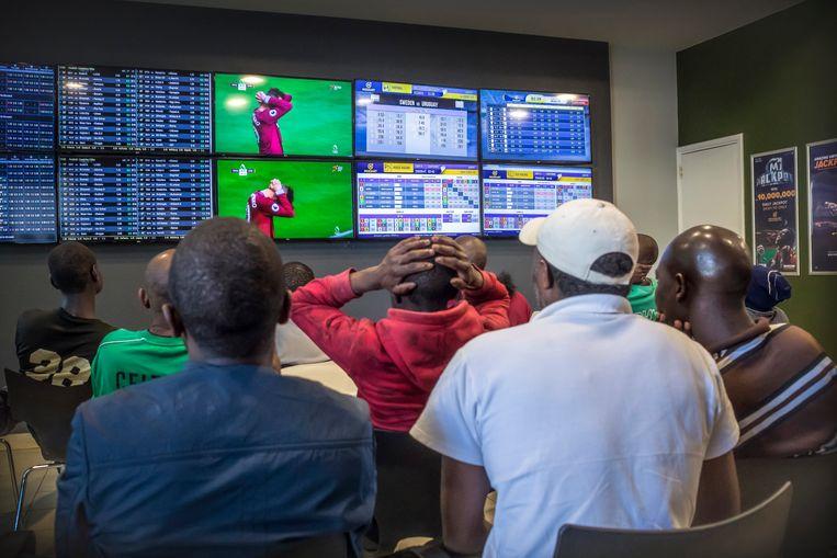 In een gokhal volgen Keniaanse mannen vol passie een voetbalwedstrijd. Beeld Sven Torfinn/Panos Pictures