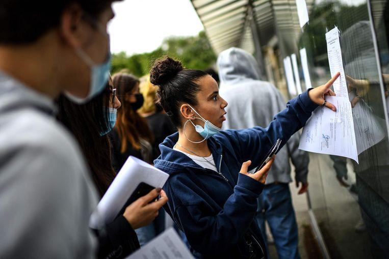 Franse leerlingen bekijken de uitslagen van hun eindexamen aan een middelbare school in Parijs. Beeld AFP