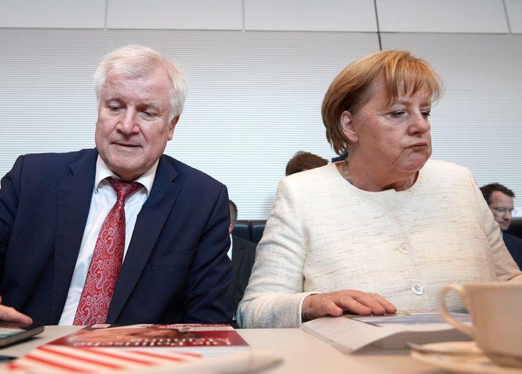 Horst Seehofer naast Angela Merkel, gisteren op de turbulente fractievergadering van de CDU en CSU. Beeld EPA