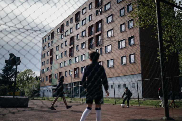 ► Jongens spelen voetbal naast een van de blokken in de Anderlechtse probleemwijk. De bewoners hekelen het optreden van de politie. Beeld Wouter Van Vooren
