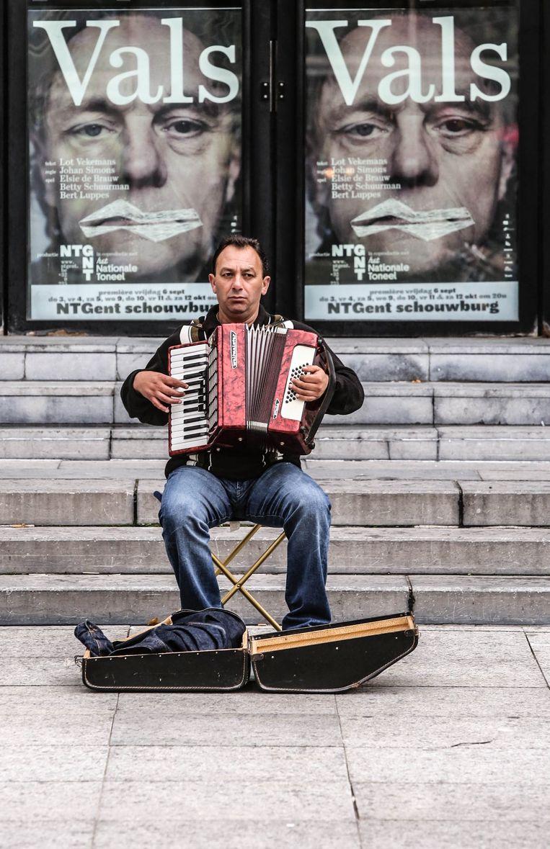 Zou de accordeonist het beseffen? Dat de affiches voor het theater in Gent achter hem niet veel goeds beloven voor de muziek die hij maakt? Beeld Henk Deleu