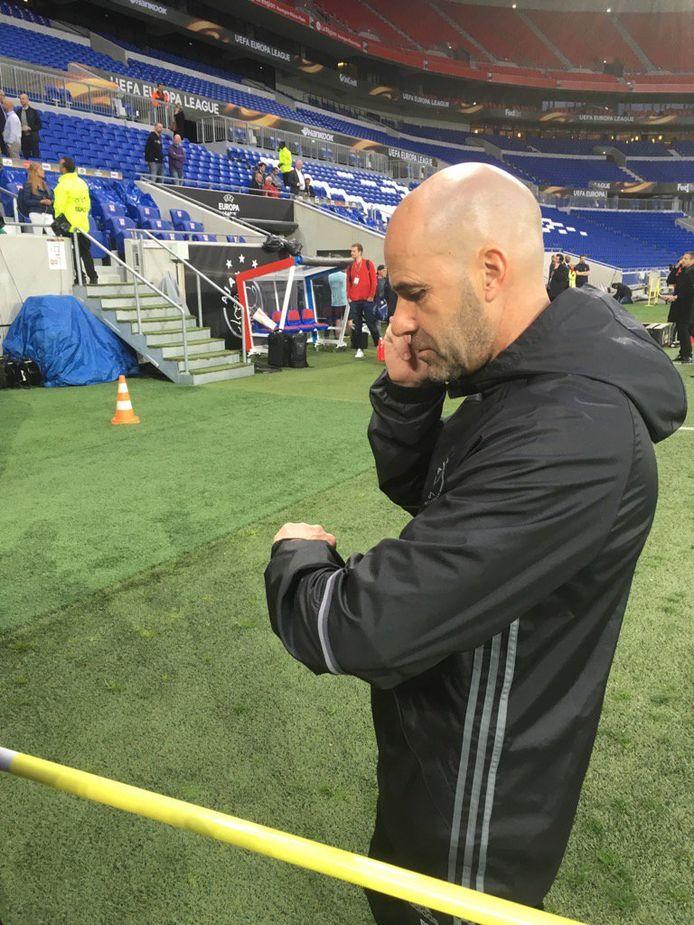 Peter Bosz geeft langs het veld in Lyon een telefonisch interview aan zijn oude Toulon-trainer Rolland Courbis.