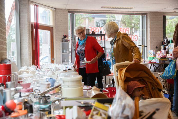 De pop-up kringloopwinkel aan de Molenstraat beleeft zaterdag aanstaande haar laatste openingsdag. In het rood vrijwilliger Nel, die de mensen graag helpt in de winkel.