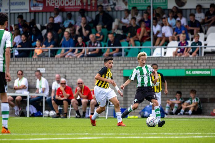 Owen Pleijsier voor een volle tribune op sportpark De Wetering aan de bal voor SC Genemuiden tegen Vitesse.