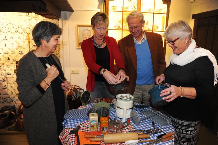 Sylvia Merrett van Dam (l) samen met andere vrijwilligers bij een tafel vol 'oud' keukenmateriaal.