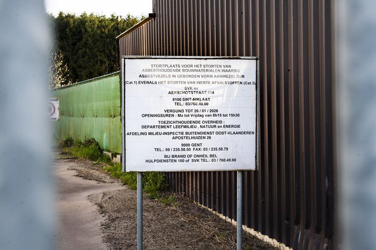 Een wit bord aan de stortplaats zegt: ''Stortplaats voor het storten van asbesthoudende bouwmaterialen waarbij asbestvezels in gebonden vorm aanwezig zijn. Vergund tot 26/01/2026.' Beeld Pieter Bogaerts