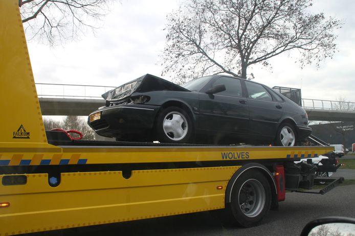 De zwaar beschadigde auto wordt afgevoerd.