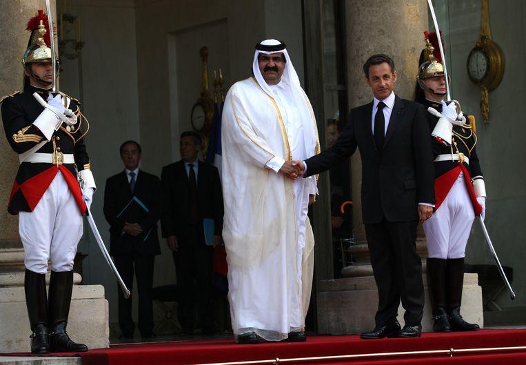 Nicolas Sarkozy schudt de hand van de emir van Qatar, sjeik Hamad Bin Khalifa Al-Thani. Beeld Corbis via Getty Images