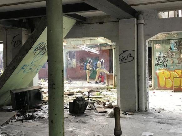 De brandweer op het gelijkvloers van de drukkerij, waar maandag het vuur ontstond.