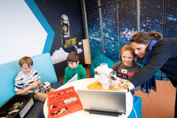 Leerlingen uit groep 5 en 6 van de Koningin Julianaschool onderzoeken in I-Space hoe een robot kunnen maken. Locatieleider Daphne Tuijtel (rechts) helpt de kinderen op weg.